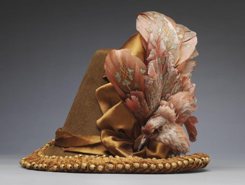 Hat, wool felt, trimmed with a starling (Sturnus vulgaris), goose or swan feathers, silk and sycamore beads, about 1885, Modes du Louvre Paris. Museum no. T.715:3-1997. © Victoria and Albert Museum, London