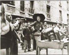 Elise Daniels with Street performers, suit by Balenciaga, Le Marais, Paris, August 1948.  thumbnail 1